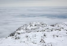Three hikers travel north along the Appalachian Trail near Mount Lafayette during the winter months in the White Mountains, New Hampshire USA